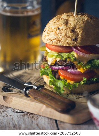 Delicious burger stacked high with a beef patty, cheese, fresh lettuce, onion and tomato on a fresh bun with sesame seed standing on brown paper with glass of beer on a wooden background - stock photo