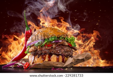 Delicious burger with fire flames - stock photo