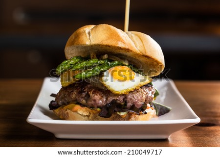 Delicious burger with onion, fried eggs, asparagus and french fries. - stock photo