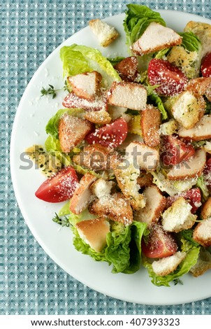 Delicious Caesar Salad with Roasted Chicken Breast, Garlic Crouton, Romaine Lettuce, Cherry Tomatoes and Grated Parmesan Cheese closeup on White Plate. Top View on Napkin - stock photo