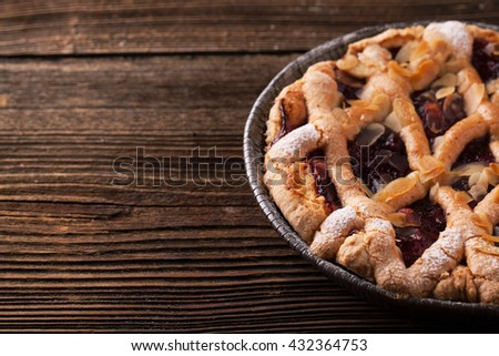 Delicious cake with cherries, icing sugar on a wooden background - stock photo