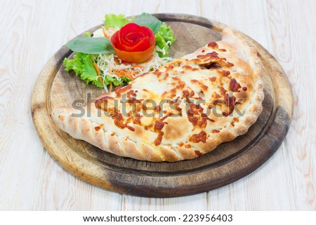 Delicious Calzone pizza on wood table - stock photo