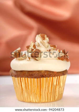 Delicious carrot cake cupcakes with cream cheese frosting and chopped pecan nuts - stock photo