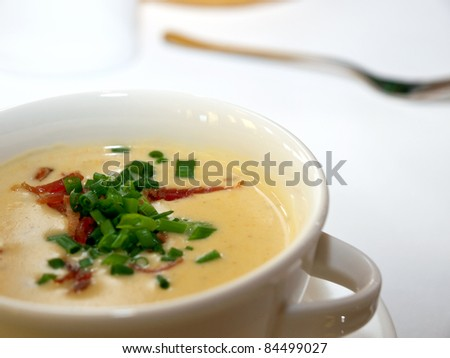 Delicious cheese cream soup with parma ham and chive in white bowl - stock photo