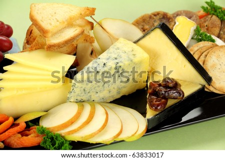 Delicious cheese platter with various cheeses and fruits ready to serve. - stock photo