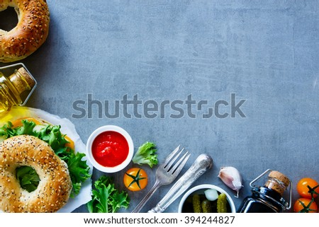 Delicious cheese sandwich on bagel with fresh vegetables over grey vintage background, border, top view, copy space. Vegetarian and healthy eating concept. - stock photo