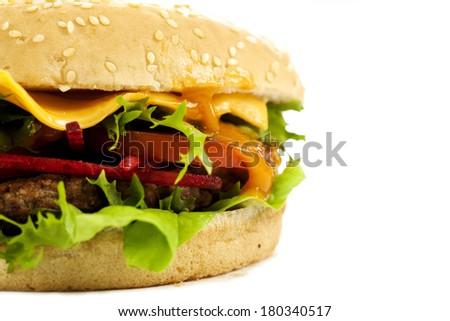 Delicious cheeseburger with beef, cheese, fresh lettuce, onion and tomato on a fresh bun with sesame seed  - stock photo
