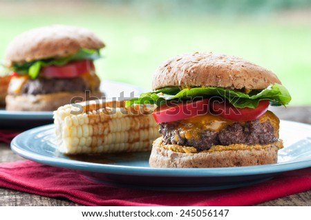 Delicious cheeseburger with corn on the cob - stock photo