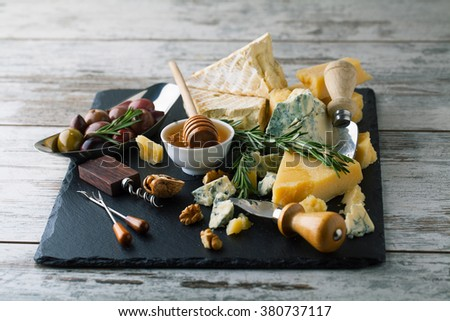 Delicious cheeses on a board with honey, nuts on a white background - stock photo