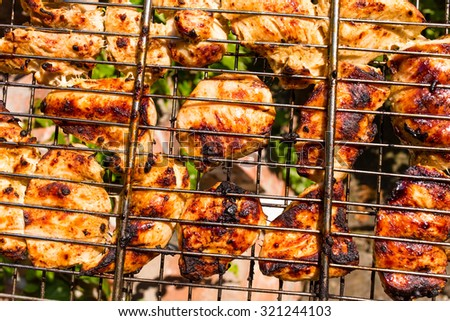 Delicious chicken on the grill closeup. Photo can be used as a whole background. - stock photo