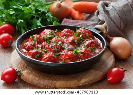Delicious chicken or turkey meatballs with rice, vegetable and  tomato sauce in frying pan/Meatballs in tomato sauce  - stock photo