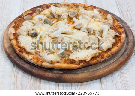 Delicious chicken pizza on wood table - stock photo