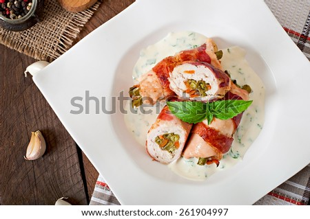 Delicious chicken rolls stuffed with green beans and carrots wrapped in strips of bacon with yoghurt and basil sauce - stock photo