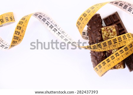 Delicious chocolate bars and peanut brittle with a measuring tape as a symbol of diet on white background copy space, horizontal photo - stock photo