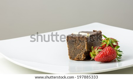 Delicious chocolate brownie and juicy strawberries on elegant white plate. - stock photo