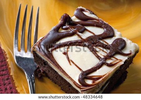 Delicious chocolate brownie with vanilla frosting on yellow place with fork - stock photo