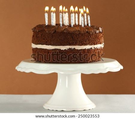 Delicious chocolate cake with candles on table on brown background - stock photo