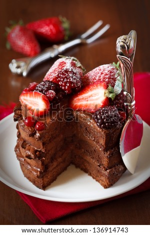Delicious chocolate cake with cream and berries close up. - stock photo
