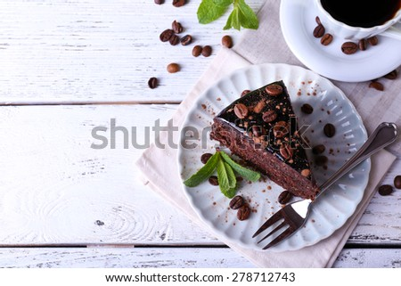 Delicious chocolate cake with mint and cup of coffee on table close up - stock photo