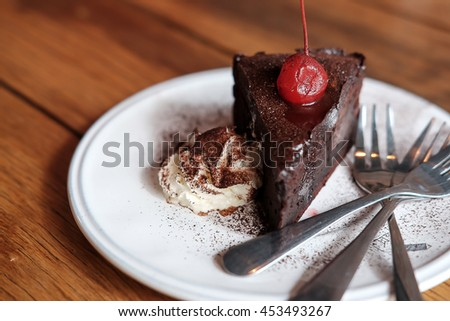 Delicious chocolate cake with red cherry  on wooden table,blurred - stock photo