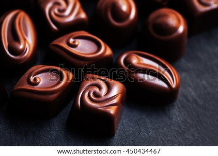 Delicious chocolate candies. Chocolates as background. Praline sweets. Low key photo - stock photo