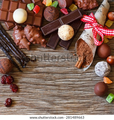 Delicious chocolates and spices on an old wooden background. - stock photo