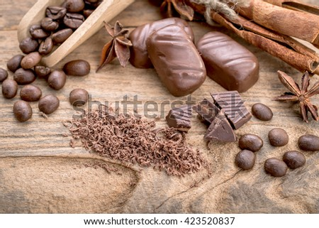 Delicious chocolates and spices on wooden background. - stock photo