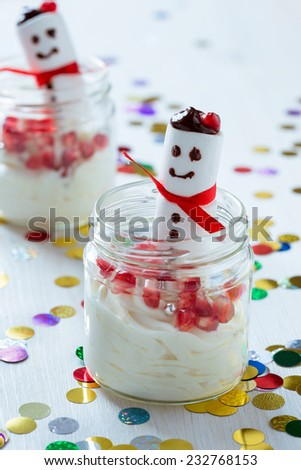 Delicious Christmas treat for dessert, cheesecake cream topped  with  sweet marshmallow snowman, served in a pretty jar - stock photo