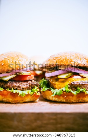 Delicious classic burger and cheeseburger on wooden board - stock photo
