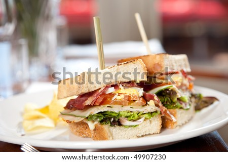 Delicious clubsandwich with toasted bread, bacon, egg, and chips - stock photo