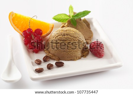 Delicious coffee ice-cream dessert served on a white platter garnished with colourful tropical fruit and coffee beans - stock photo