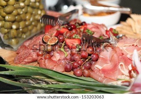 Delicious cold cuts on a wood tray. - stock photo