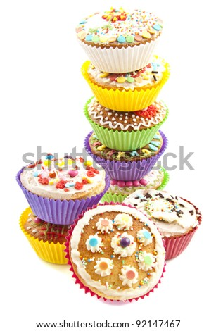 Delicious colorful cupcakes on a pile over white - stock photo