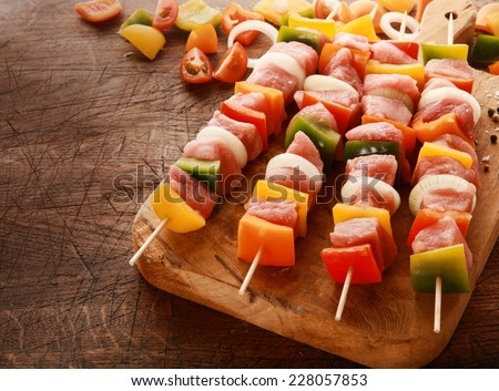 Delicious colorful meat and vegetable kebabs waiting to be cooked laid out ready on a wooden board on an old grungy table in a rustic kitchen, high angle view - stock photo