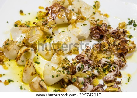 Delicious cooked squid or calamari plate with olive oil - stock photo