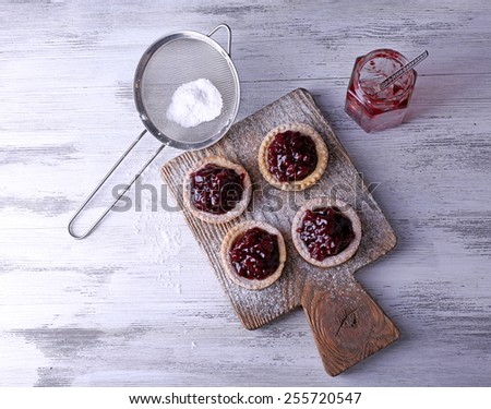 Delicious cookies with jam and powdered sugar on cutting board on wooden background - stock photo