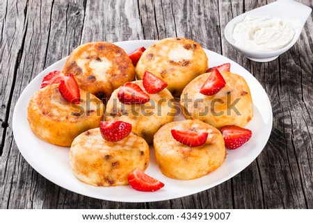 Delicious Cottage cheese pancakes with raisins and strawberries - stock photo