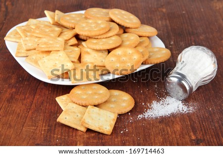 Delicious crackers with salt on wooden background - stock photo
