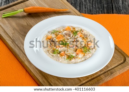 Delicious creamy cheese mushroom soup with spring carrots and spices, decorated with dill, in a white wide rim dish on a cutting board on an old rustic table, horizontal close-up - stock photo