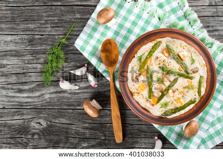 Delicious creamy cheese mushroom soup with spring carrots, asparagus and spices, decorated with dill, in a clay bowl on a table napkin with wooden spoon on an old rustic table, horizontal  top view - stock photo