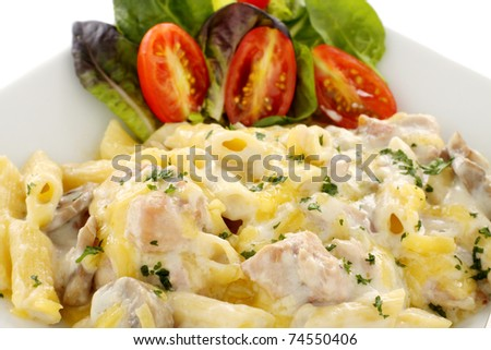 Delicious creamy chicken penne pasta with a garden salad. - stock photo