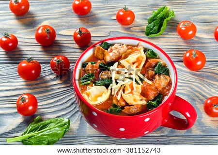 Delicious creamy tomato soup with tortellini, Italian sausages, spinach, decorated with parmesan cheese in a red mug on a table, close-up, top view, selective focus - stock photo