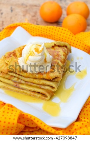 Delicious crepes with orange syrup and whipped cream on white plate (Crepe Suzette) - stock photo