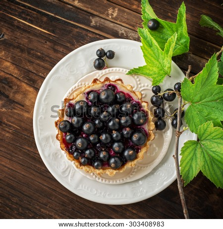 Delicious crispy tarts with black currants on wooden table, closeup - stock photo