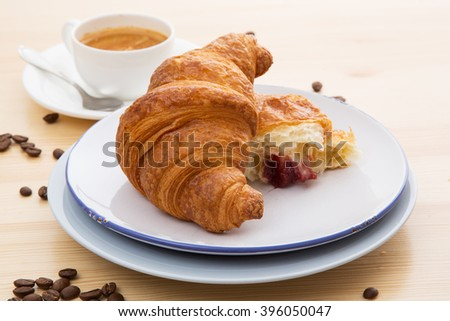 Delicious croissant with a cup of coffee - stock photo