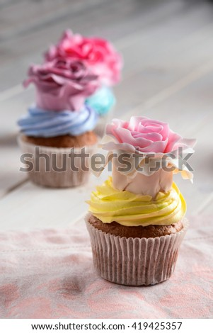 Delicious cupcake in front of the camera on accurate napkin. Gentle pink rose on yellowish cream of the bakery. Bright colorful confection in the blurred background. Tasty snack for everyone. - stock photo