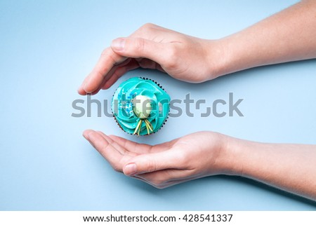 Delicious cupcake with cream in hands on a blue background - stock photo