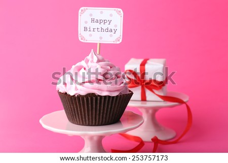 Delicious cupcake with inscription on pink background - stock photo