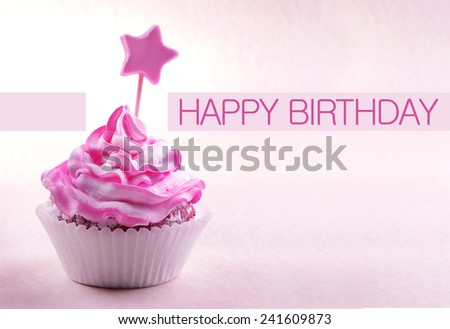 Delicious cupcake with star on stick and Happy Birthday text on light pink background - stock photo