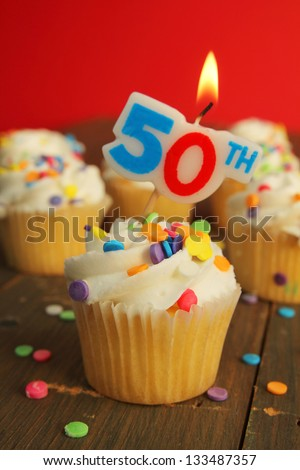 Delicious cupcake with 50th candle on top and 49 other cakes in background - stock photo